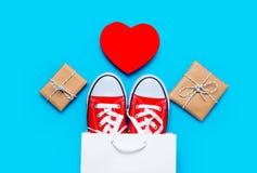 Grands chaussures en caoutchouc rouges dans le panier frais, le jouet en forme de coeur et le beau Photo libre de droits