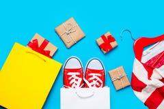 Grands chaussures en caoutchouc rouges dans le panier frais, veste rayée sur le cintre Photo stock