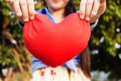 Grands coeur et fond rouges des mains de fille ou de femmes Photographie stock