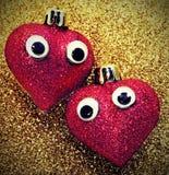 Grands coeurs rouges dans l'amour avec des yeux dans le glitte d'or de fond Image stock