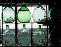 Grands dames - jeannes en verre pour le vin contre la lumière d'une fenêtre image stock