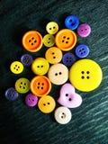 Grands et petits boutons de couleur sur le noir image stock