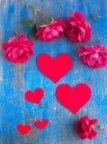 Grands et petits coeurs et beaucoup rose rouge sur le bleu Photographie stock libre de droits