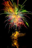 Grands feux d'artifice colorés au-dessus de l'eau Photographie stock libre de droits