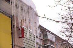 Grands glaçons glacés pendant du toit de la maison image libre de droits