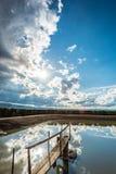 Grands nuages avec le soleil de starburst et réflexions dans l'eau photographie stock