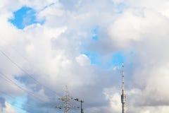 Grands nuages blancs au-dessus de tour et de ligne électrique de TV Photographie stock libre de droits