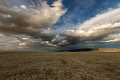Grands nuages gonflés au-dessus d'un désert desséché Photo stock