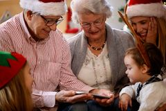 Grands-parents avec des enfants regardant des photos de Noël sur le phone de cellules Image libre de droits