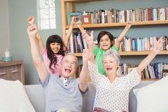 Grands-parents avec des petits-enfants faisant des gestes le signe de succès Photographie stock