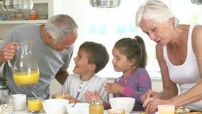 Grands-parents avec des petits-enfants faisant le petit déjeuner dans la cuisine clips vidéos