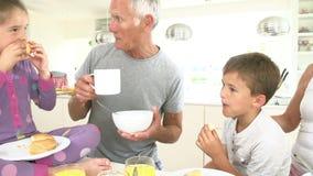 Grands-parents avec des petits-enfants mangeant le petit déjeuner dans la cuisine banque de vidéos