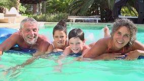 Grands-parents avec des petits-enfants sur le matelas pneumatique dans la piscine banque de vidéos