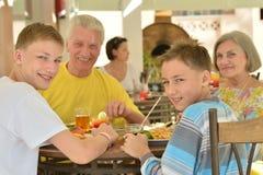 Grands-parents avec l'petit-enfant au petit déjeuner image libre de droits