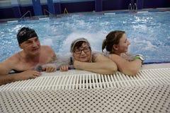 Grands-parents avec la petite-fille se reposant dans la piscine Photographie stock libre de droits