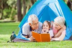 Grands-parents avec le livre de lecture de petite-fille dedans Photos libres de droits