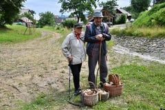 Grands-parents avec le panier des champignons après l'automne répandant dans la forêt photo stock