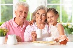 Grands-parents avec le thé potable de petite-fille Photo stock