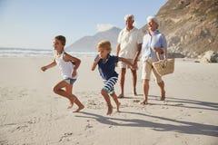 Grands-parents courant le long de la plage avec des petits-enfants images libres de droits