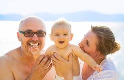 Grands-parents de portrait et petit petit-enfant appréciant des vacances de plage image libre de droits