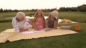 Grands-parents dessinant avec la petite-fille dehors banque de vidéos