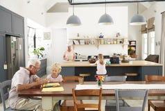 Grands-parents et grandkids passant le temps dans la cuisine de famille photographie stock