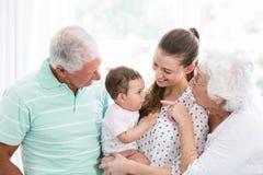 Grands-parents et mère de sourire jouant avec le bébé image stock