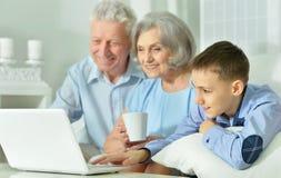 Grands-parents et petit-fils à l'aide de l'ordinateur portable Image stock