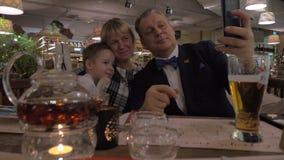 Grands-parents et petit-fils faisant le selfie pendant le dîner de famille dans le restaurant banque de vidéos