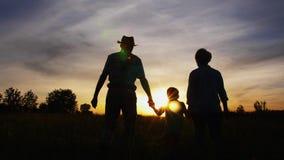 Grands-parents et petit petit-fils marchant au coucher du soleil clips vidéos