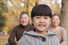 Grands-parents et petite-fille en parc, souriant et regardant l'appareil-photo Photos stock