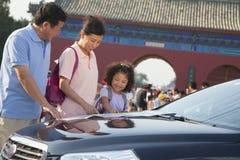 Grands-parents et petite-fille se tenant à côté de la voiture et regardant la carte Photos stock