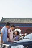 Grands-parents et petite-fille se tenant à côté de la voiture et regardant la carte Photo libre de droits