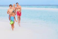 Grands-parents et petits-enfants ayant l'amusement des vacances de plage Photos libres de droits