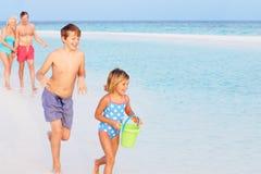 Grands-parents et petits-enfants ayant l'amusement des vacances de plage Images stock
