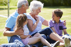 Grands-parents et petits-enfants jouant le football dans le jardin Photo stock