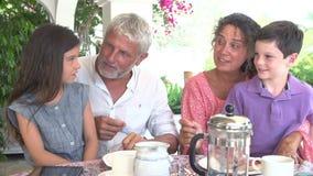 Grands-parents et petits-enfants prenant le petit déjeuner ensemble banque de vidéos