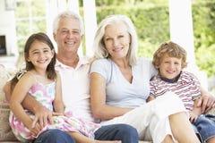 Grands-parents et petits-enfants s'asseyant sur Cane Sofa At Home photos stock