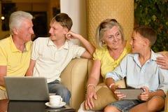Grands-parents et petits-fils avec les dispositifs numériques Photos stock
