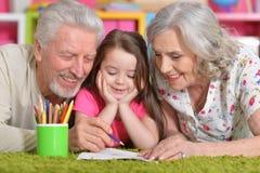 Grands-parents jouant avec le grandaughter Photos stock