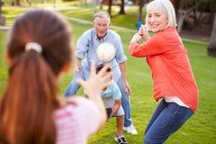 Grands-parents jouant le base-ball avec des petits-enfants en parc images stock