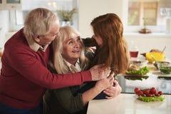 Grands-parents joyeux tenant la petite fille dans la cuisine Photos libres de droits