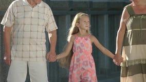 Grands-parents marchant avec leur petite-fille banque de vidéos