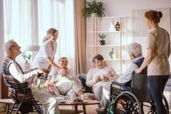 Grands-parents passant le temps dans la chambre commune avec leurs travailleurs sociaux images stock