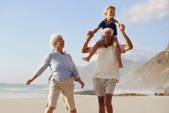 Grands-parents portant le petit-fils sur des épaules sur la promenade le long de la plage photographie stock libre de droits