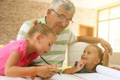 Grands-parents travaillant le travail avec des petite-filles Images stock