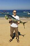 Grands poissons de fixation de touristes sur la plage photographie stock