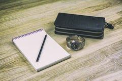 Grands portefeuille, carnet, crayon et montre-bracelet du ` s d'hommes sur la texture en bois photos libres de droits