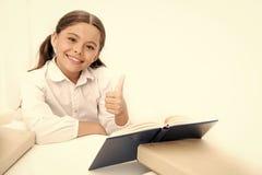 Grands pouces jusqu'? l'enseignement ? domicile Peu livre de le?on de lecture de fille ? la maison   petit images libres de droits