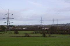 Grands pylônes et câbles portant l'électricité produite à la puissance Stationy de Ballylumford dans la grille Photographie stock libre de droits